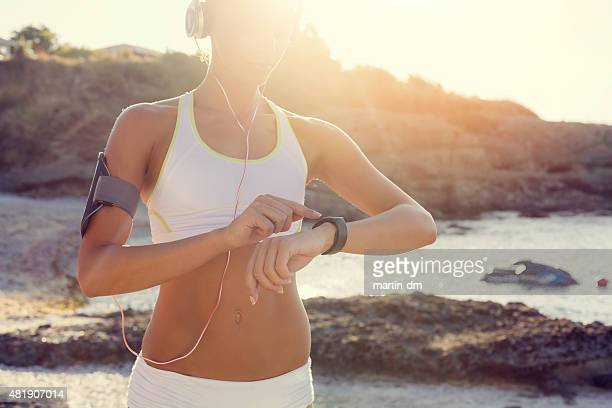 Sports woman at the beach using smart watch