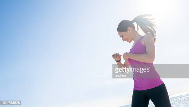 sports woman checking her pulse on a smart watch - checking sports stock pictures, royalty-free photos & images