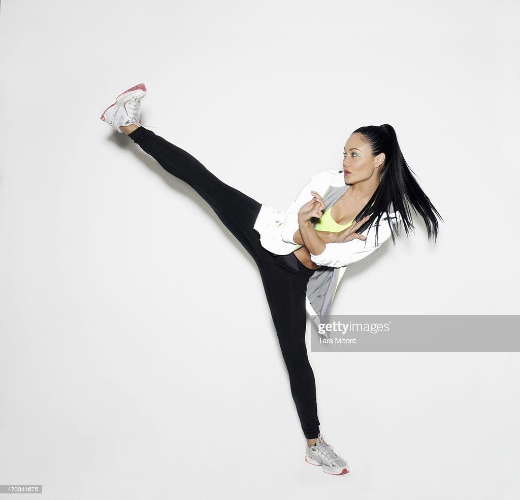 sports woman doing karate kick