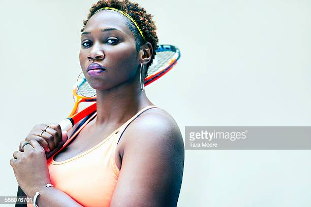 Sports woman in gym clothes with tennis racket