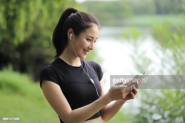 Sports woman listening to music with earphones