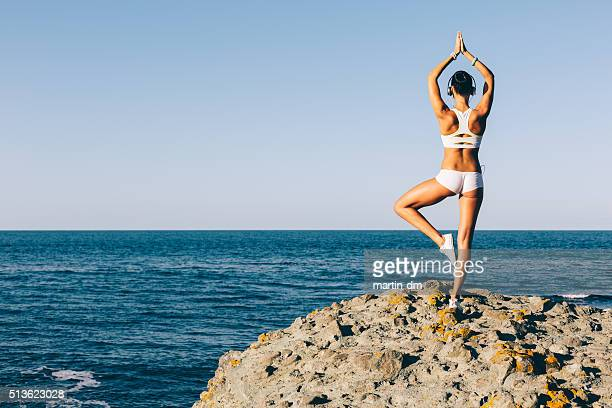 Sports woman meditating at the beach