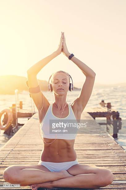 Sports woman meditating at the quay