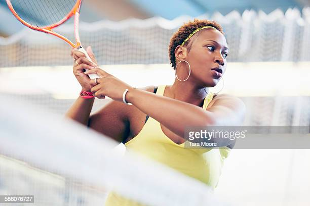 sports woman on tennis court swinging racket - tennis stock pictures, royalty-free photos & images