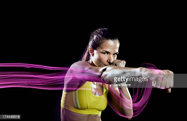 sports woman punching air with light trails