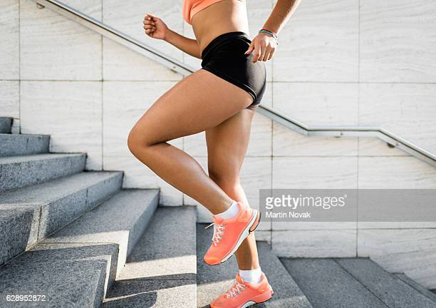 sports woman running upstairs. fitness and sport concept. - nalgas fotografías e imágenes de stock