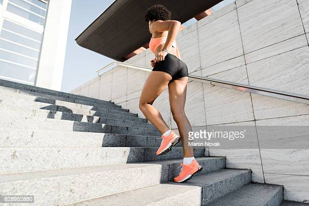 Sports woman running upstairs. Fitness and sport concept.