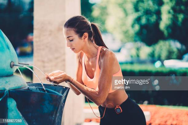 Sports woman splashing with water at the fountain