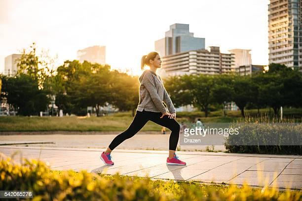 ストレッチスポーツの女性日没での街、大阪(日本)
