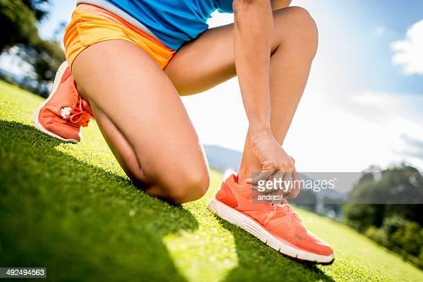 スポーツの女性彼女の靴紐結束