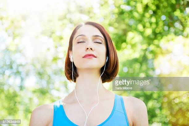 sports woman with eyes closed wearing headphones