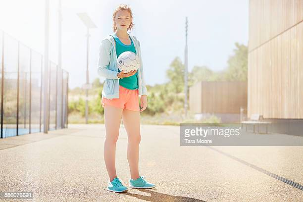 Sports woman with football outside pitch