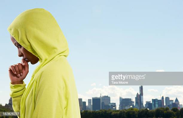 sports woman with hooded top in city