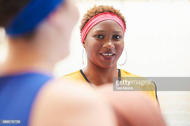 sports women in gym clothes chatting at the gym - 輪っかのイヤリング ストックフォトと画像
