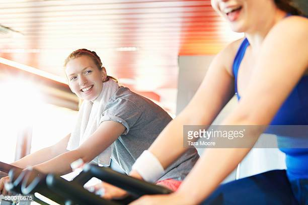Sports women in gym clothes training on gym bikes