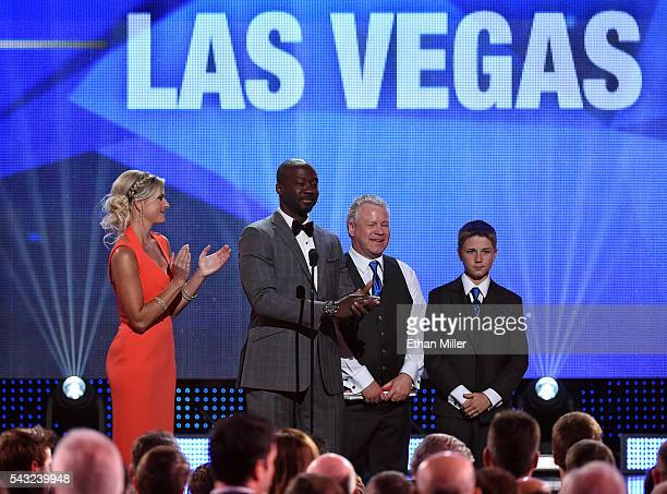 Sportscaster Kathryn Tappen hockey analyst Anson Carter Gerry Nelson and his son Wyatt Nelson present the Bill Masterton Memorial Trophy during the...
