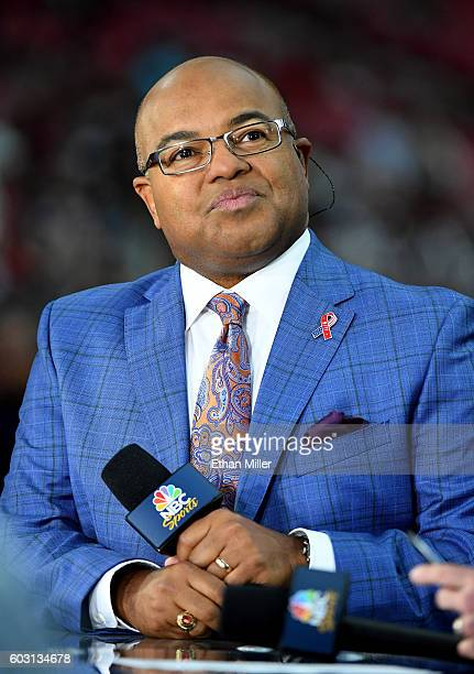 Sportscaster Mike Tirico sits on the Sunday Night Football set before the NFL game between the New England Patriots and the Arizona Cardinals at...