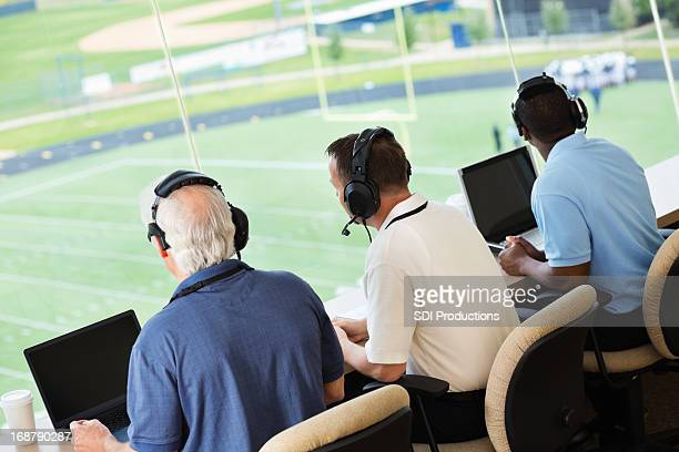 sportscasters watching and calling a football game in press box - commentator stock pictures, royalty-free photos & images