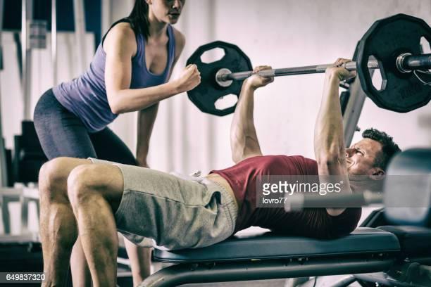 ジムでベンチプレスをしているスポーツマン。