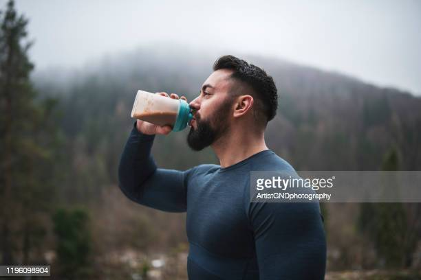 sportsman drinking protein outdoor - protein drink stock pictures, royalty-free photos & images