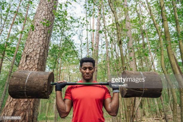 sportsman exercising with wooden barbells in the forest - levantamento de peso imagens e fotografias de stock