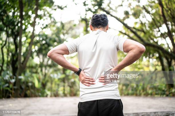 スポーツマンは公園で腰痛を感じる - 下背部痛 ストックフォトと画像