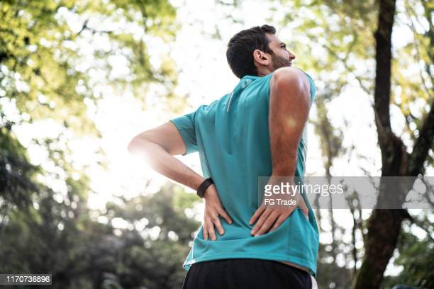 sportsman feeling backache at a park - back pain stock pictures, royalty-free photos & images