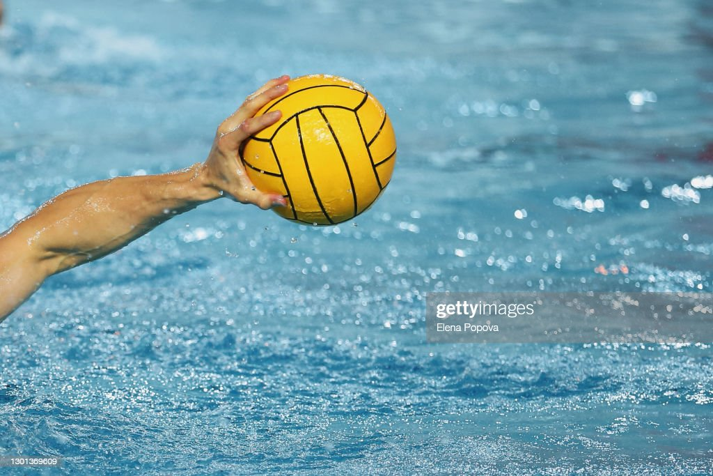Sportsman Holding a Water Polo Ball above the water : Stock Photo