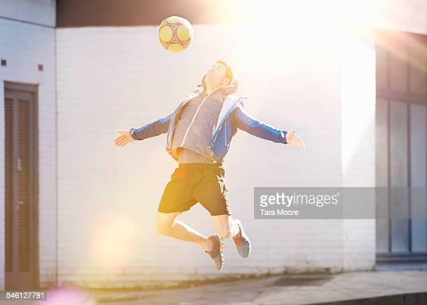 Sportsman jumping in air with football in street