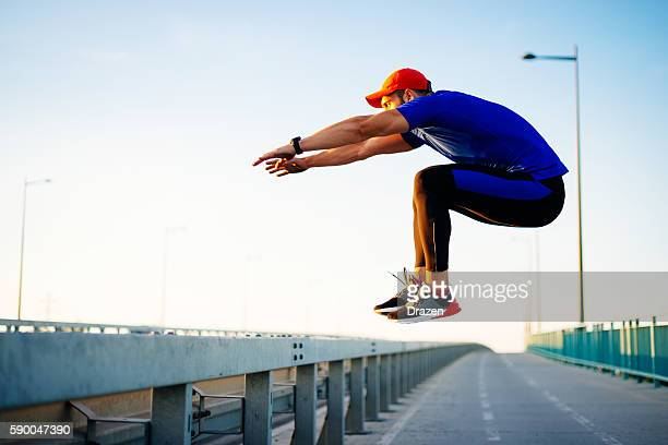 Sportsman jumping over barriers during parkour training