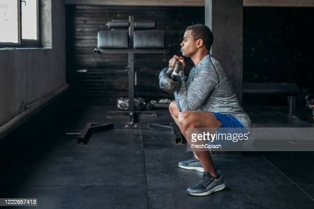 sportsman lifting weights at a gym gym - crouching stock pictures, royalty-free photos & images