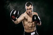 Sportsman muay thai boxer fighting in gloves in boxing cage. Isolated on black background with smoke. Copy Space.