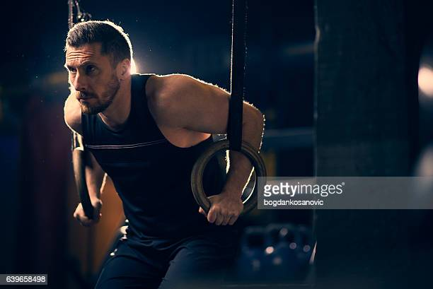 Sportsman performing ring dips in the gym
