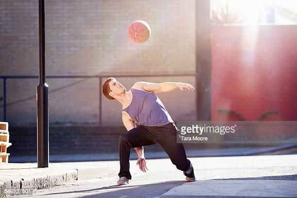 Sportsman playing basketball in urban street