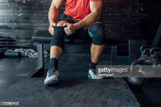sportsman putting on a knee sleeve at the gym - long sleeved stock pictures, royalty-free photos & images