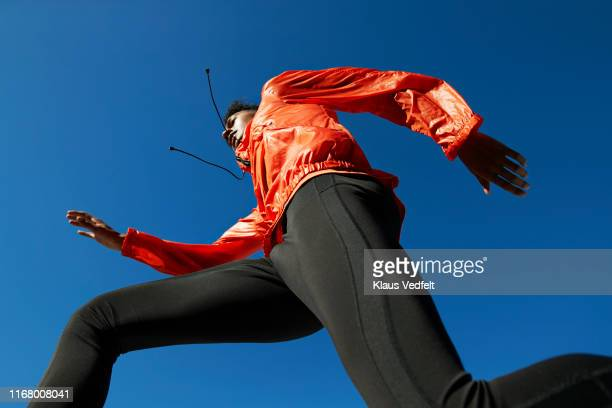 sportsman running against clear blue sky during sunny day - blue coat stock pictures, royalty-free photos & images