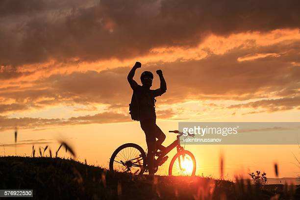 Sportsman standing on top of the hill with hands raised