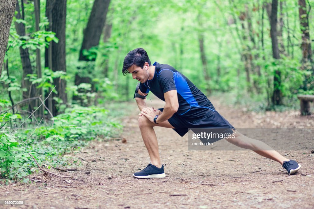 Sportsman stretching legs before workout : Stock Photo