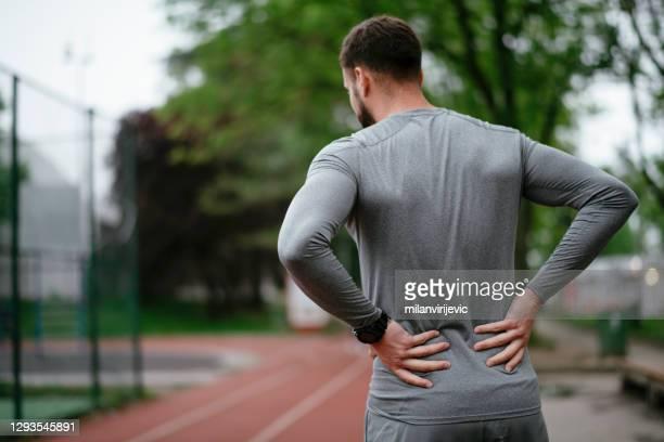 屋外の公園で腰痛に苦しむスポーツマン - 下背部痛 ストックフォトと画像