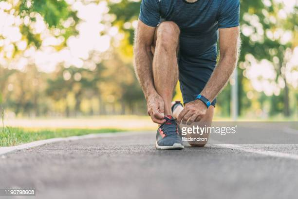 sportsman tying shoelaces - shoelace stock pictures, royalty-free photos & images