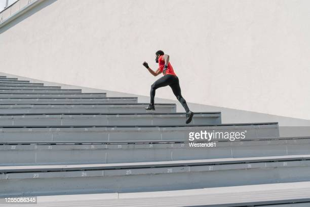sportsman wearing face mask running up stairs - success stock pictures, royalty-free photos & images