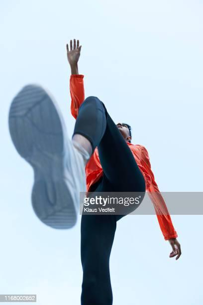 sportsman with legs apart against clear sky - ângulo esporte - fotografias e filmes do acervo