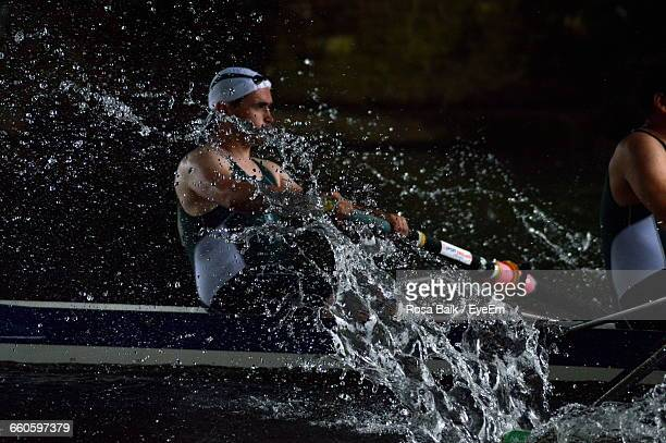 sportsmen rowing boat in river - rowing stock pictures, royalty-free photos & images
