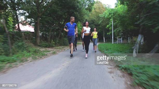 Sportspeople running on road in nature
