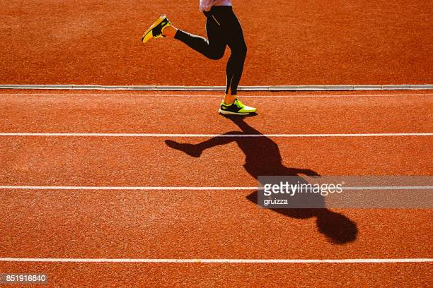 sportsperson running over the running track - orange shoe stock photos and pictures
