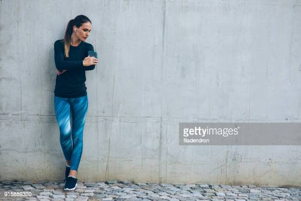 sportswoman checking her arm band - leggings stock pictures, royalty-free photos & images