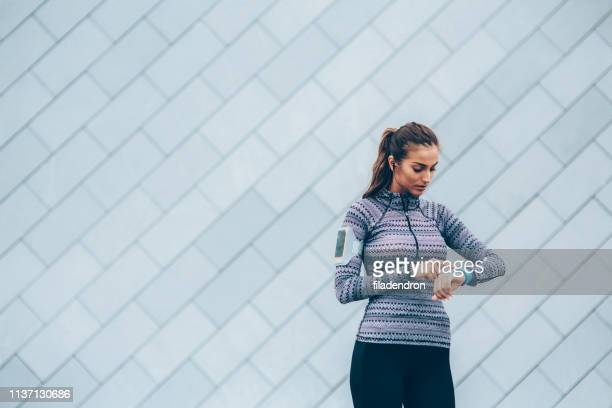 sportswoman checking her smart watch - activity stock pictures, royalty-free photos & images