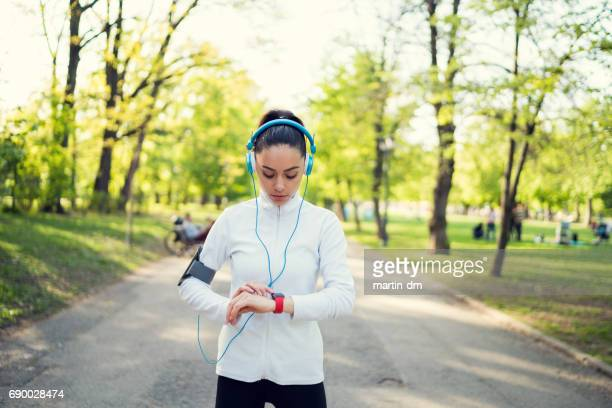 Sportswoman checking pulse on smart watch