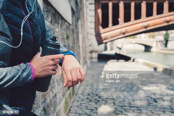 sportswoman checking pulse on smart watch - fitness tracker stock pictures, royalty-free photos & images