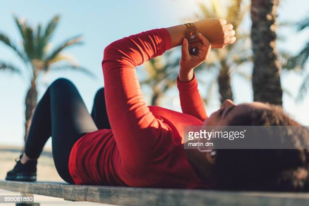 sportswoman checking pulse on smartwatch - smart watch stock pictures, royalty-free photos & images